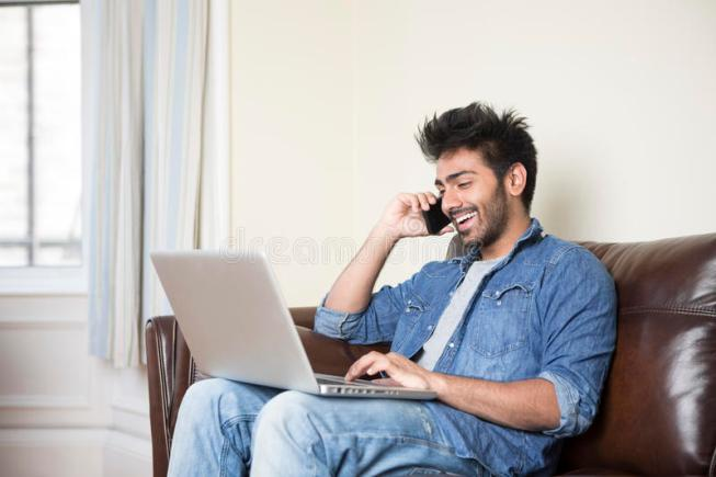 indian-man-using-laptop-phone-home-asian-talking-lounge-54889365